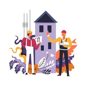 Costruttori che lavorano su grafici di piani di lettura di costruzioni di case