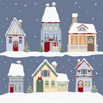 Edifici coperti di neve, decorati con ghirlande e ghirlande per le vacanze di natale. celebrazione degli eventi stagionali invernali, natale e capodanno. case con alberi di pino all'aperto. vettore in stile piatto