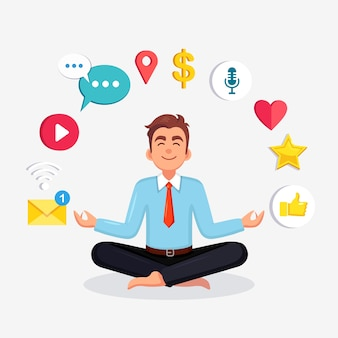 Uomo d'affari che fa yoga con social network, icona dei media. lavoratore seduto nella posa del loto padmasana