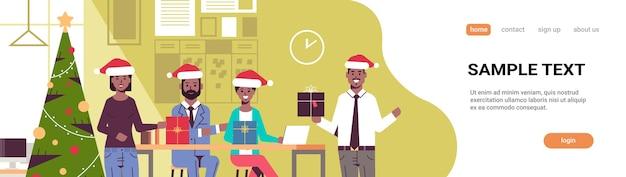 Uomini d'affari che celebrano la festa aziendale colleghe in possesso di scatole regalo buon natale felice anno nuovo concetto di vacanze pagina di destinazione interni ufficio moderno
