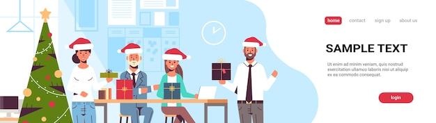 Uomini d'affari che celebrano la festa aziendale colleghe in possesso di scatole regalo presente buon natale felice anno nuovo concetto di vacanze invernali moderno ufficio pagina di destinazione