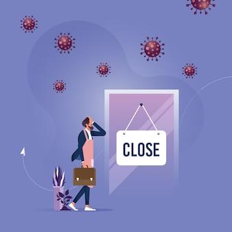 Proprietario del negozio di affari con segno chiuso e agente patogeno del virus covid