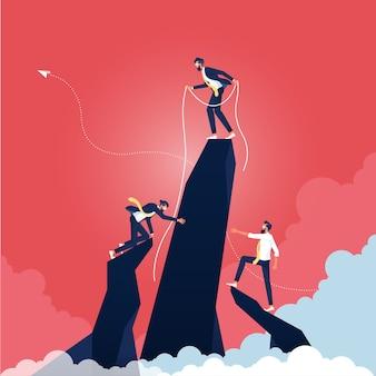 Il team aziendale si aiuta a vicenda in cima alla montagna