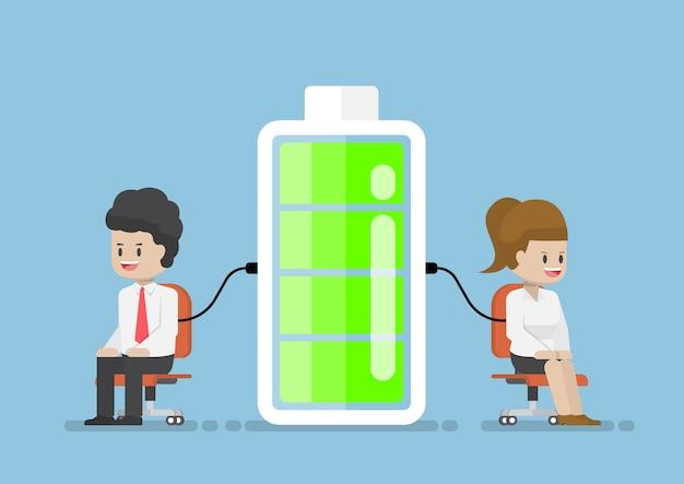 Carattere dell'uomo d'affari e della donna di affari che carica il potere di energia dalla batteria