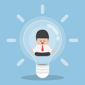 Uomo d'affari che fa meditazione all'interno della lampadina, concetto di idea