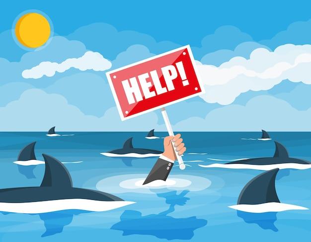 Uomo d'affari che annega in mare con gli squali. equipaggia la mano con il segno di aiuto.