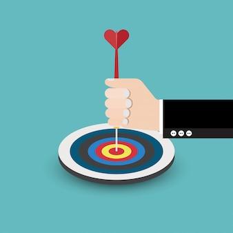 La mano dell'uomo d'affari tiene una freccia all'obiettivo