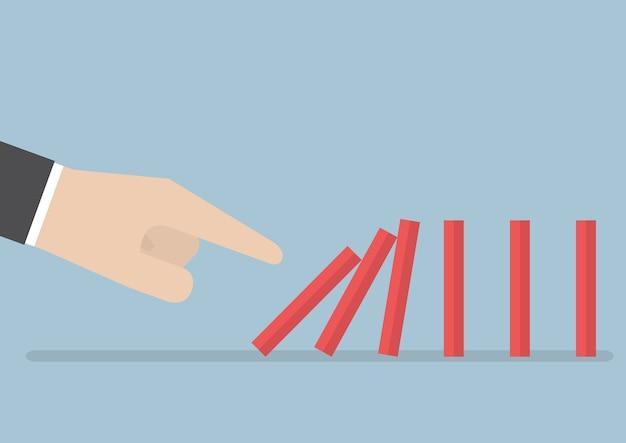 Mano di uomo d'affari che spinge l'effetto domino