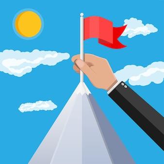 La mano dell'uomo d'affari mette la bandiera sulla cima della montagna.
