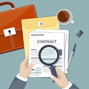 Mani dell'uomo d'affari che tengono la lente d'ingrandimento sopra un contratto, vista dall'alto