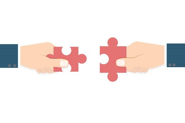 Mani dell'uomo d'affari che tengono puzzle. concetto di lavoro di squadra.