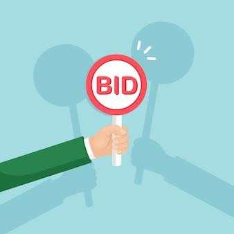Pala dell'asta della stretta dell'uomo d'affari in mano. offerte, concetto di concorrenza all'asta. le persone salgono cartelli con iscrizioni bid. processo commerciale aziendale.