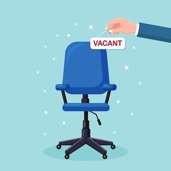 Imprenditore tenere premuto segno vacante in mano sopra la sedia da ufficio.