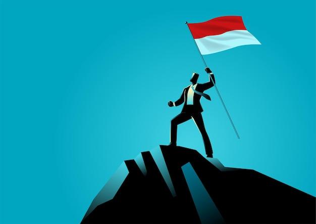 Uomo d'affari che tiene la bandiera dell'indonesia in cima alla montagna