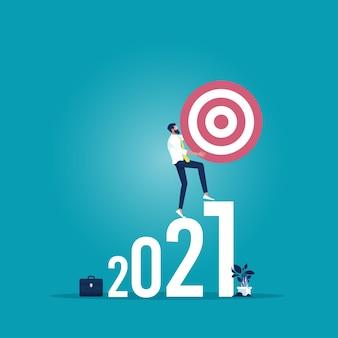 Uomo d'affari che tiene l'obiettivo e cammina sul numero 2021 verso l'obiettivo, il successo, la carriera, la crescita del concetto di business verso il successo nel 2021