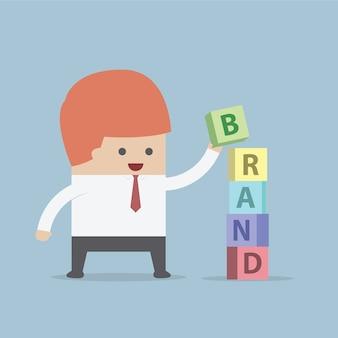 L'uomo d'affari sta costruendo la parola di marca, concetto della costruzione di marca