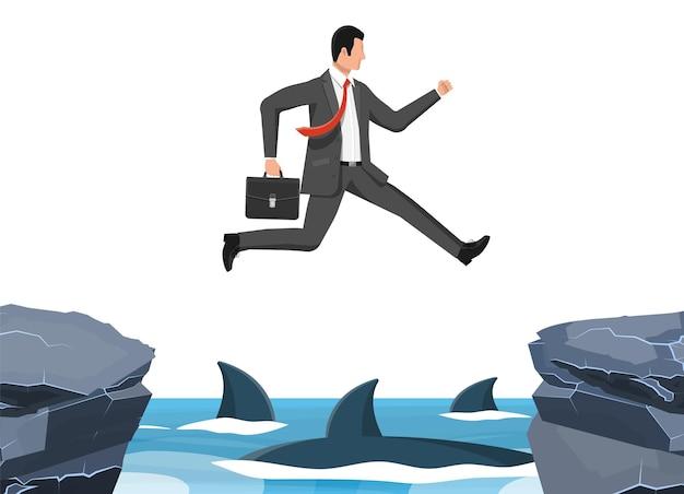 Uomo d'affari che salta su uno squalo in acqua