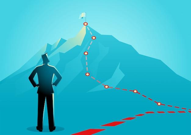 Uomo d'affari che osserva le linee rosse che conducono alla cima di una montagna