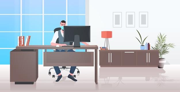 Uomo d'affari in maschera seduto sul posto di lavoro protezione dall'epidemia di coronavirus di allontanamento sociale
