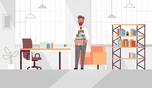 Scatola moderna della tenuta dell'impiegato di concetto dell'uomo d'affari con l'interno moderno dell'ufficio del posto di lavoro creativo di affari di lavoro della roba di cose della roba