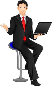 Uomo d'affari in posa e tenendo il computer portatile