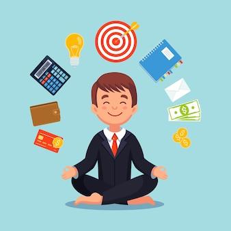 Uomo d'affari che pratica la meditazione di consapevolezza con le icone dell'ufficio sullo sfondo. multitasking e concetto di gestione del tempo. l'uomo pratica lo yoga nella posizione del loto