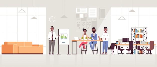 Uomo d'affari che presenta grafico finanziario sulla lavagna a fogli mobili al gruppo delle persone di affari all'orizzontale integrale interno moderno dell'ufficio di lavoro moderno di concetto di presentazione di riunione di conferenza