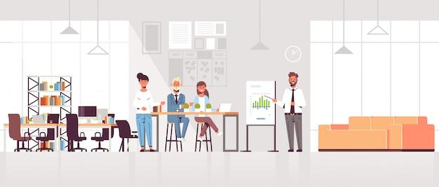 Uomo d'affari che presenta grafico finanziario sulla lavagna a fogli mobili al gruppo delle persone di affari alla riunione di conferenza che prepara l'interiore moderno dell'ufficio di spazio di lavoro congiunto di presentazione