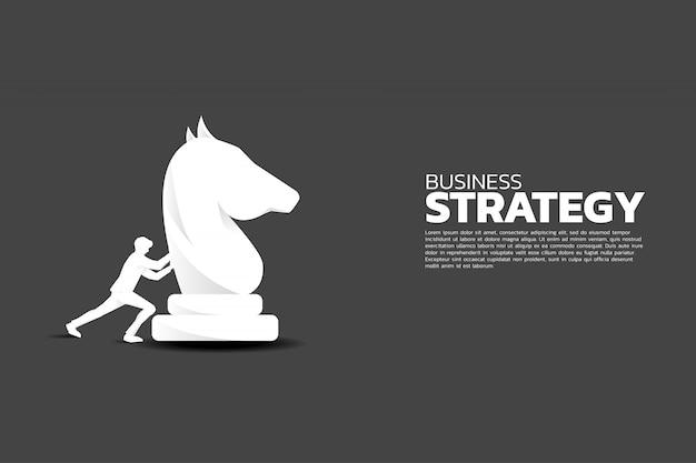 Pezzo degli scacchi cavaliere push uomo d'affari.