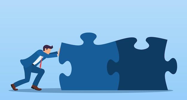 Uomo d'affari che spinge i pezzi dei puzzle. concetto di business di problem solving congiunto.
