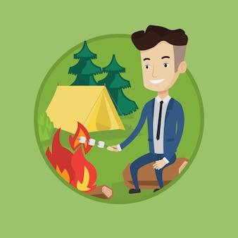 Caramella gommosa e molle di torrefazione dell'uomo d'affari sopra il fuoco di accampamento.