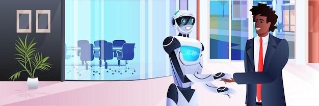 Uomo d'affari e robot di handshaking durante la riunione accordo di partenariato intelligenza artificiale concetto di tecnologia