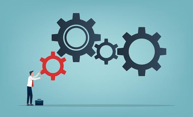 Uomo d'affari che rotola un piccolo ingranaggio rosso al simbolo di grandi ingranaggi. concetto di business e aumento dell'efficienza e della produttività.