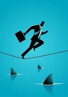 Uomo d'affari che funziona sulla corda con gli squali sotto