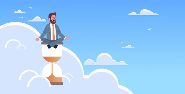 Posizione di loto di seduta dell'uomo d'affari sull'orologio della sabbia nel termine di gestione di tempo del cielo concetto dell'uomo d'affari che medita posa yoga orizzontale maschio carattere integrale