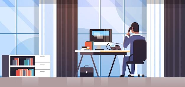 Uomo d'affari che si siede all'uomo di affari di retrovisione dello scrittorio del posto di lavoro facendo uso del computer mentre parlando sull'orizzontale creativo dell'interno interno dell'ufficio di concetto di processo di lavoro del telefono della linea fissa