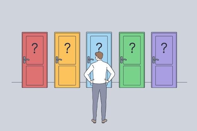 Imprenditore in piedi all'indietro davanti a porte colorate