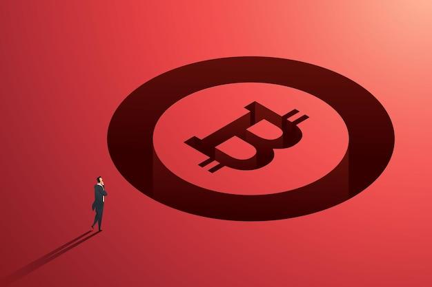 Uomo d'affari in piedi di fronte a un gigantesco token bitcoin che investe sulla volatilità del rischio di criptovaluta