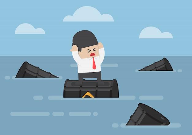 Uomo d'affari che sta sui barili da olio nell'oceano