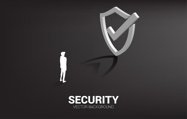 Uomo d'affari che sta con l'icona dello scudo di protezione 3d. concetto di guardia di sicurezza
