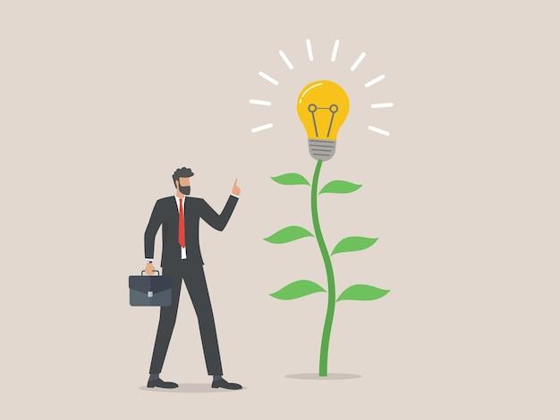 L'uomo d'affari sta a un albero della lampadina, idea di affari, successo