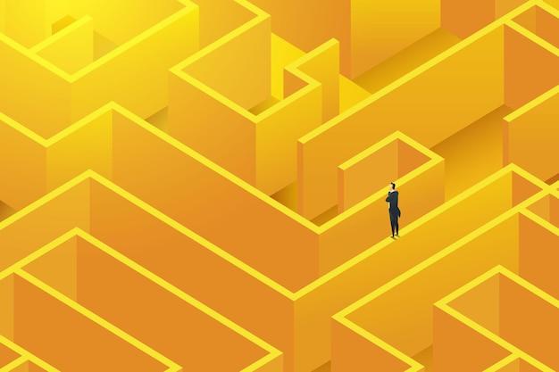 L'uomo d'affari sta sulla parete di un grande labirinto complesso per trovare soluzioni alla decisione delle sfide
