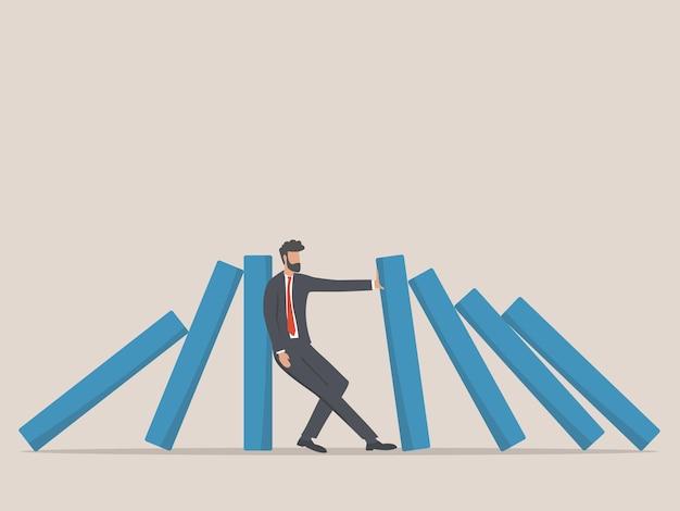 Uomo d'affari che ferma la caduta del domino. simbolo di crisi, rischio, gestione, concetto di leadership.