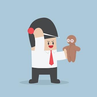 L'uomo d'affari prova a pungere l'ago in una bambola di voodoo