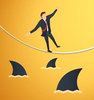 Uomo d'affari che cammina sulla corda con gli squali sotto