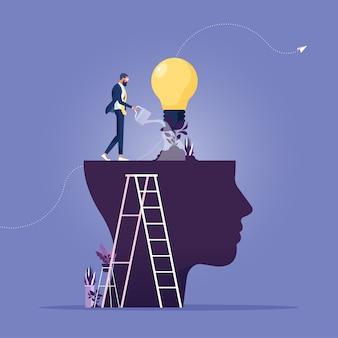 Uomo d'affari che innaffia quella pianta lampadina crescente dal cervello come personalità di crescita metafora