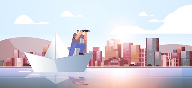 Uomo d'affari con il binocolo che galleggia sulla barca di carta alla ricerca di una pianificazione strategica della strategia di avvio della leadership futura
