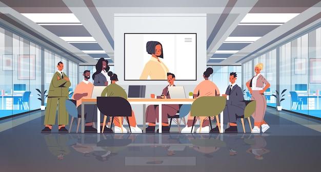 Imprenditori che hanno conferenza in linea mix gara uomini d'affari che discutono con imprenditrice durante la videochiamata ufficio sala riunioni interni figura intera