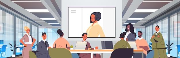 Imprenditori con conferenza in linea mix gara uomini d'affari che discutono con imprenditrice durante la videochiamata ufficio sala riunioni illustrazione interna