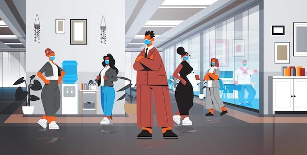 Gli uomini d'affari in maschere protettive che stanno insieme il concetto di quarantena del coronavirus mescolano i colleghi della corsa che discutono durante la riunione illustrazione integrale dell'interno dell'ufficio moderno